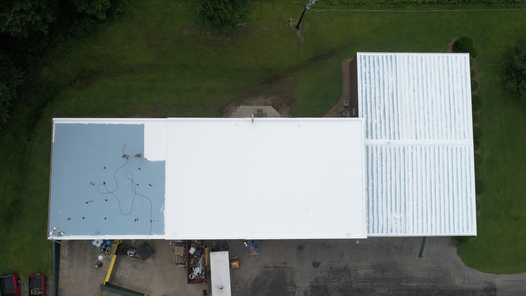 a flat commercial roof in progress of being coated