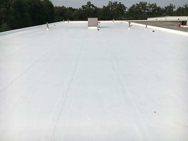 Commercial pvc membrane flat roof completely restored to a white, waterproof, energy efficient roof by applying a fresh Flexion membrane system