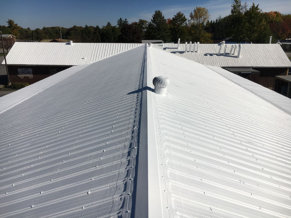 Low slope metal roof after its been restored using an SPF spray foam coating by Keystone Commercial Roofing