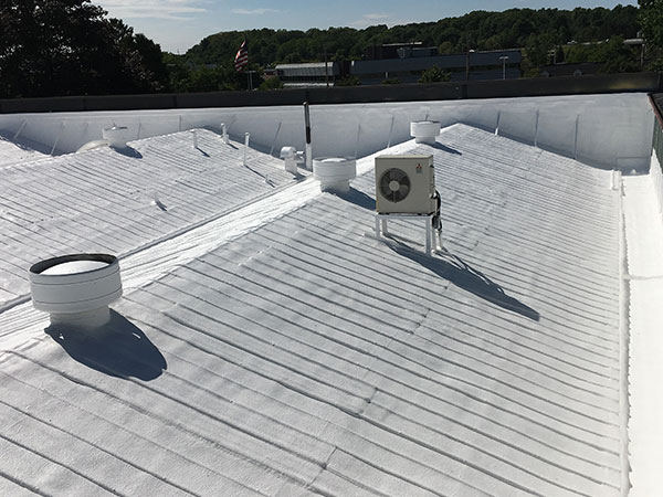 Commercial metal roof restored using an SPF spray foam roofing system