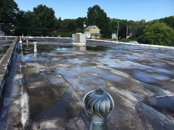 Badly weathered, blackened commercial FLexion (PVC) membrane flat roof