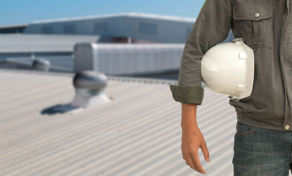 Man with a hard hat standing on a commercial metal roof