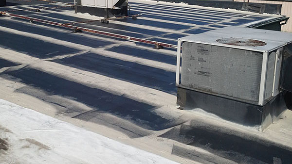 Commercial flat roof being restored with a membrane coating