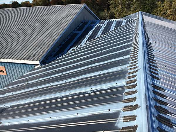 Worn out, low slope commercial metal roof ready to be restored by commercial roofing specialists from Keystone Commercial Roofing
