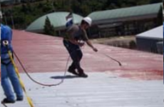 Roofing expert applying primer to low slope, commercial metal roof