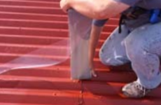 Roofing repair specialist applying seam treatment to a commercial metal roof