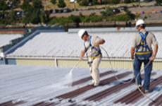 Metal roofing specialist applying the finish coat on a commercial metal roof