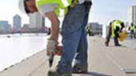 Roofing expert cleaning & priming a commercial roof for restoration
