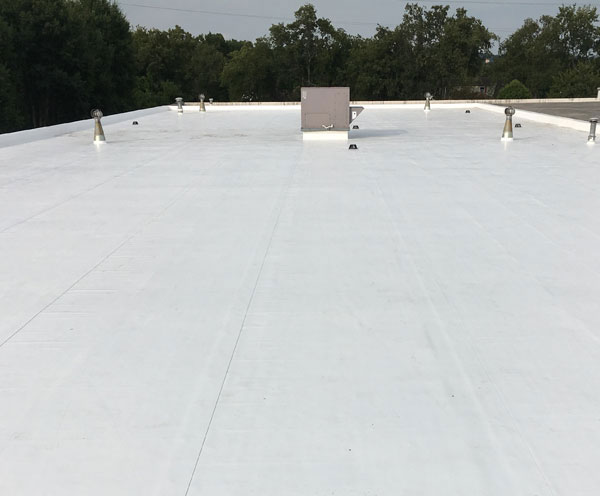 Flat commercial roof restored utilizing a single-ply membrane roofing system